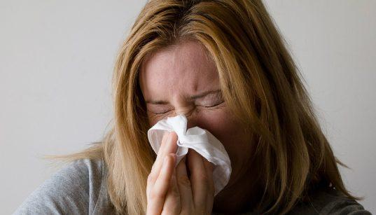 Influenzás nő orrot fúj